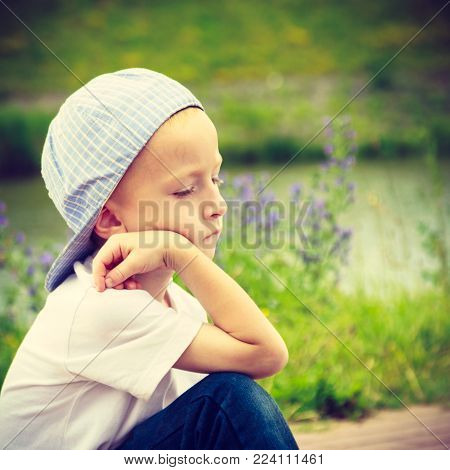Pensive boy child thinking and daydreaming. Thoughtful kid leaning on his hand looking forward. Imagination.