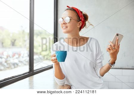 Indoor Shot Of Fashionable Woman In Eyewear, Waits For Friend At Cafe Or Restaurant, Enjoys Favourit
