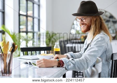 Cheerful Bearded Male Guy In Stylish Denim Jacket, Hat And Eyewear Reads Magazines While Sits At Kit
