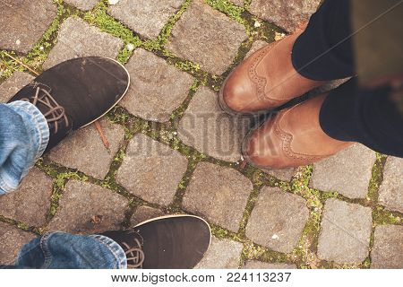 Man and woman. Autumn concept. Female legs in brown leather boots stand next to the man's legs dressed in shoes and standing on an ancient stone road overgrown with green moss
