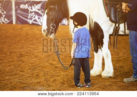 Ber Yakov, Israel - September 28, 2016: Horse riding lessons for kids. The boy near the horse