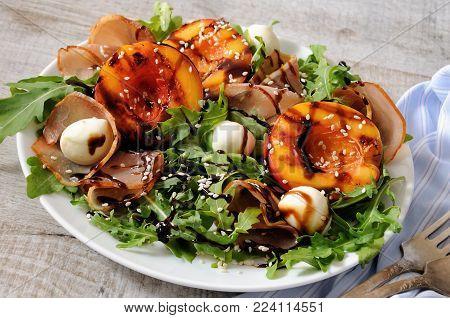 Salad with dried ham, grilled nectarine, mozzarella and arugula