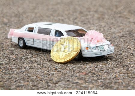 Bitcoin golden coin near model of luxury white car on asphalt background. Wedding, Bitcoin accepted and Financial concept