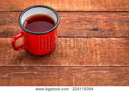 red metal cup of hot tea on a rustic wooden picnic table with a copy space
