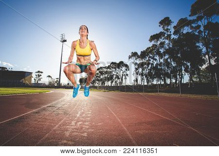 Female Fitness Model And Track Athlete Sprinting On An Athletics Track Made From Tartan