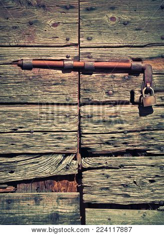 Antique wooden door with lock and padlock. Worn and worn wood, rusty lock.