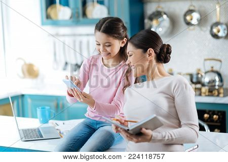 I cherish you. Lovely joyful dark-haired girl smiling and showing photos on her photos to her mom while sitting on the kitchen table