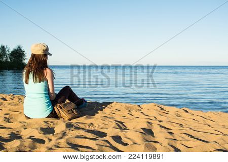 Young traveller woman in blue top with dark hair with cap and bag sitting on sand and looking at sea and blue sky far away