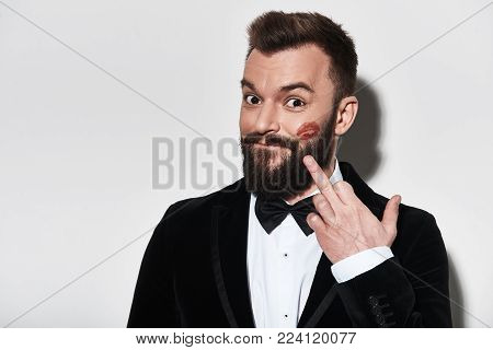 Ladies love him! Handsome young man in full suit pointing at lipstick marks and smiling while standing against grey background