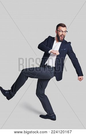 On the way... Full length of handsome young man in formalwear making a face and gesturing while walking against grey background