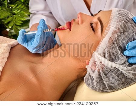 Filler injection for female forehead face. Plastic aesthetic facial surgery in beauty clinic Silicone lips in girl Doctor with syringe injects lips augmentation Spring discounts for visiting spa salon