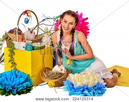Easter dresses for women. Girl holding bunny and eggs. Woman with holiday hairstyle and make up touch rabbit in basket with flowers. Easter discounts. Breeding of domestic animals.