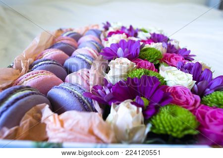 French macaroon cake. Violet and pink macaroons in a box with flowers on the bed.