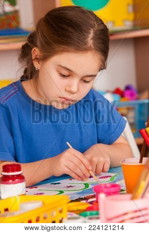 Small students painting in art school class. Child drawing by paints on table. Girl in kindergarten. Drawing education develops creative abilities of children. Spring flowers drawings.