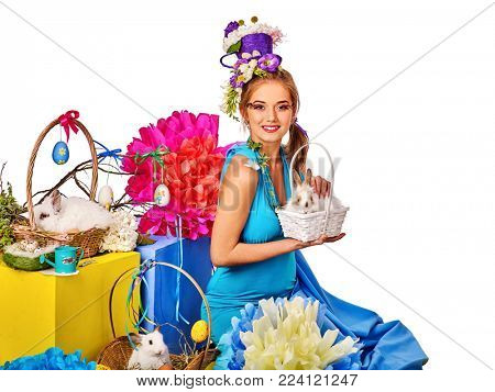 Easter girl holding bunny and eggs. Spring woman with holiday hairstyle and make up holding rabbit in basket with flowers. White background. Preparation for Easter.