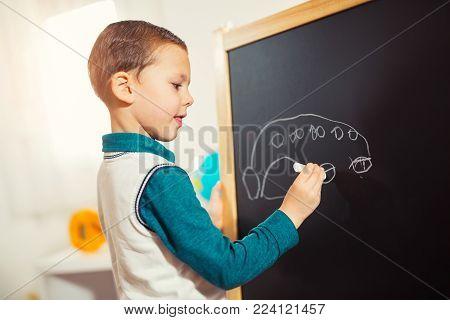 Scribbles, little boy drawing with chalk on blackboard.