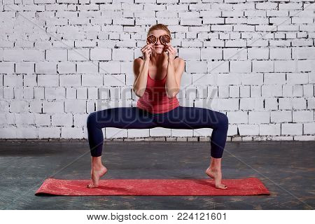 Young attractive smiling woman practicing yoga. Sporty pretty woman loves sports. Beautiful athletic women holding slices as glasses, half sitting on the mat. Girl practicing yoga concept, pilates, fitness training, wearing sportswear, white brick backgro