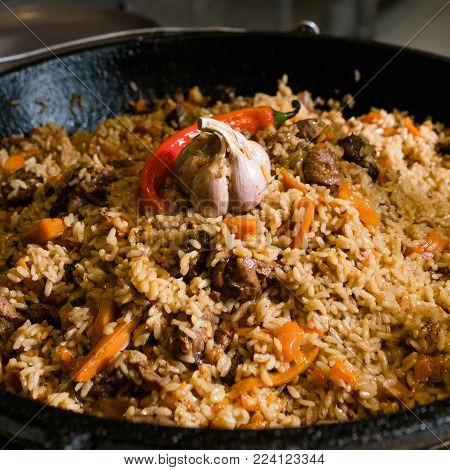 ethnic cuisine. The dish of pilaf. Traditional Uzbek food. Meat and rice plov meal