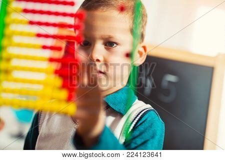 Cute little boy counting with abacus at home