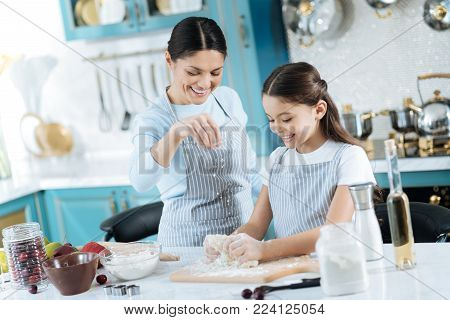 Baking with pleasure. Pretty alert dark-haired schoolgirl and mother smiling and making some dough for cookies while wearing pinafores