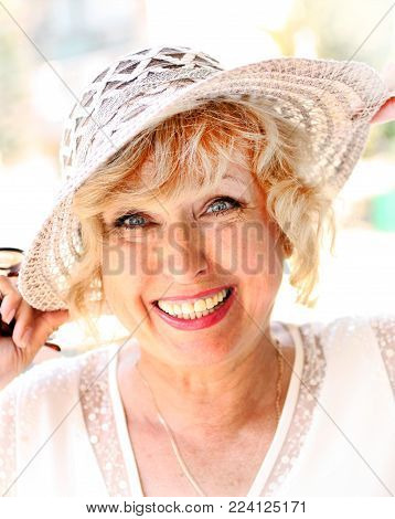 Portrait of smiling attractive elegant senior lady in hat. Living positively beautiful mature woman. Positive attitude towards life. Vertical.