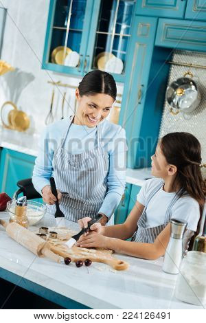 Happy motherhood. Pretty content dark-haired daughter and her mother making some delicious cookies and using pastry brushes and rolling pin lying on the table