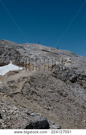 Stone Path among Barren Mountains, Wooden Christian Cross and Worshippers in Italian Dolomites Alps in Summer Time.