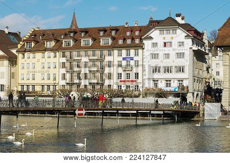 LUCERNE, SWITZERLAND - FEBRUARY 20, 2012: Unidentified people walk by the bridge with the historical buildings at the background in Lucerne, Switzerland.