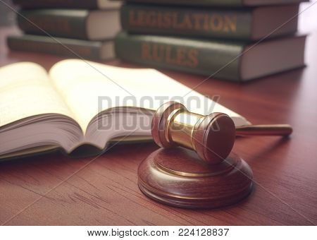 3D illustration. Wooden hammer with gold details and books in the background.