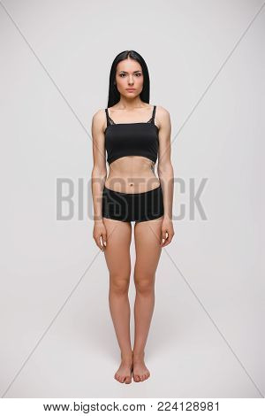 serious young brunette woman in black underwear standing on gray studio background. full length photo