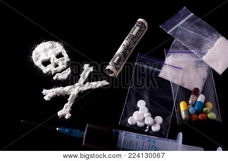 Drug dependence Kills. A line of cocaine in the form of a skull and a roll of a dollar, sachets with a dose, pills, syringe. Black background. Addiction concept