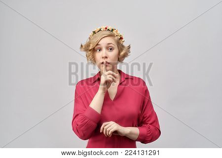 attractive young girl with short curly blond hair in a classic red dress with flower wreath on head, puts a finger to her lips and asking to keep quiet or secret. Close-up portrait on white background