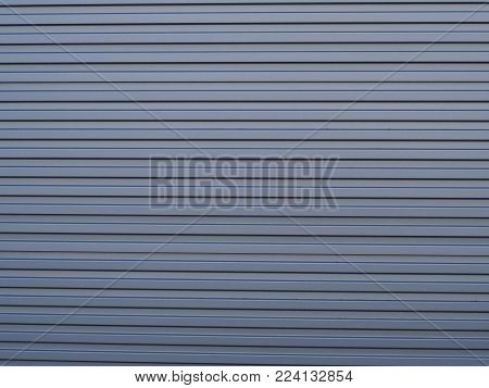 Authentic striped corrugated steel wall. Genuine, weathered, textured and striped corrugated steel wall. Great as a background for construction and industrial, or strength and coolness, or safety earthquake, shelter, security and protection amongst others poster