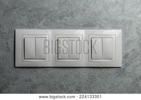 Group of white switches on gray wall close-up