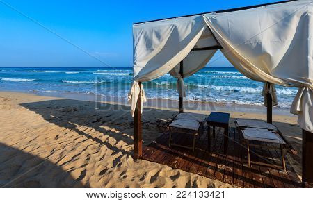 Luxury beach tents canopies on morning paradise white sandy beach ( Salento, Puglia, south Italy). The most beautiful sea sandy beach of Apulia.