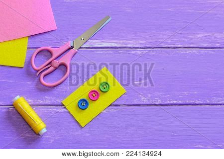 Multicolored buttons sewn to the yellow felt piece. Scissors, thread, felt pieces on a wooden background with copy space for text. How to sew a button quickly and prettily. Top view