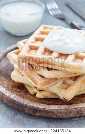 Homemade savory belgian waffles with bacon and shredded cheese, served with plain yogurt, on a wooden plate, vertical