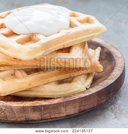 Homemade savory belgian waffles with bacon and shredded cheese, served with plain yogurt on a wooden plate, square format
