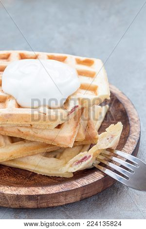Homemade savory belgian waffles with bacon and shredded cheese, served with plain yogurt on a wooden plate, vertical, copy space