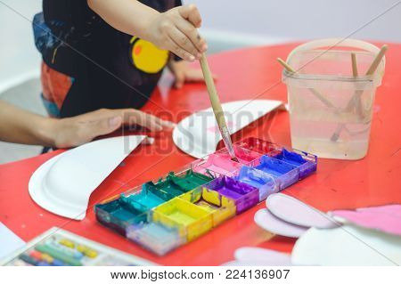Close up of paint brush in hand of Asian toddler painting with watercolors in colorful palette at art class, kid painting with nursery teacher ,Creative play for toddlers concept, Selective focus