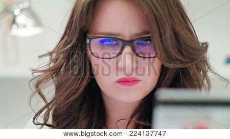 A young lady holding a credit card indoors. Close-up Dolly shot. Soft focus.