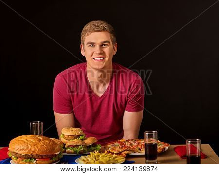 Man eating hamburger , pizza and plate of French fries. Fastfood concept. Spring discounts for fast food. Lunch for student.