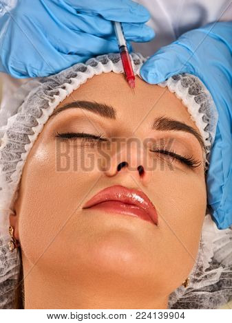 Filler injection female forehead face. Plastic aesthetic facial surgery in beauty clinic cosmetic procedure. Doctor in medical gloves with syringe injects removal of forehead wrinkles and facelift.