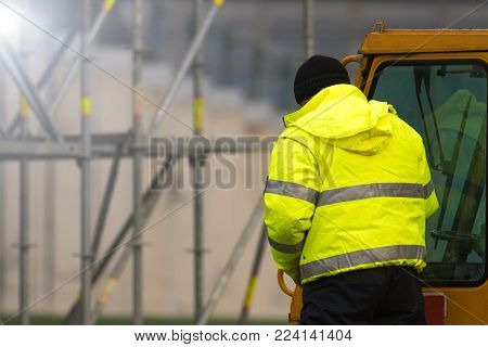 Forklift driver in yallow at the construction site
