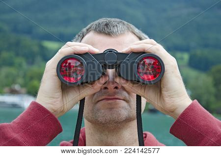 A middle-aged man with a binoculars observing nature at the lake