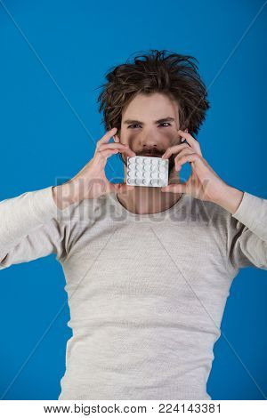 Man With Pills In Blister Pack Has Uncombed Hair In Morning On Blue Background, Health And Medicine,