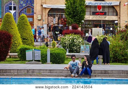 Isfahan, Iran - April 24, 2017: A young Iranian couple is sitting near a mosque in front of a fountain on a date and gaily chatting, the Naqsh-e Jahan Square.
