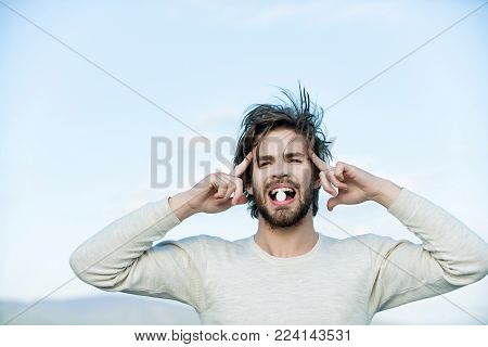 Man With Pill In Mouth Has Uncombed Hair In Morning Outdoor On Sky Background, Health And Medicine,