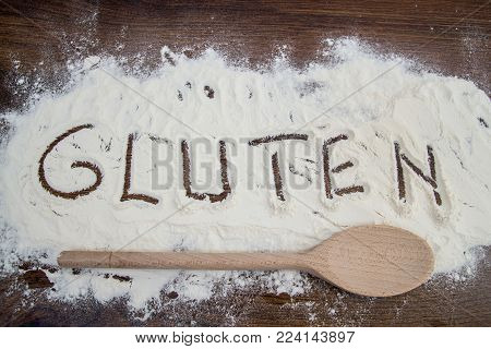 Wooden spoon and white flour on cooking table. Word gluten written on wheat flour.