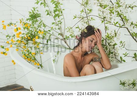 Sexy Woman In Bathtub At Spring Blossom, Spa. Spring Relax In Bathroom. Beauty And Spa, Health, Well